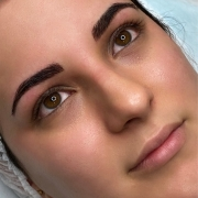 Youn woman's face looking up while esthetician perform a permanent makeup microblading and shading in Portland Oregon. Ombré Powder Microblading Hair stroke (with the machine), Lip blush, Eyeliner, Eyelash enhancement